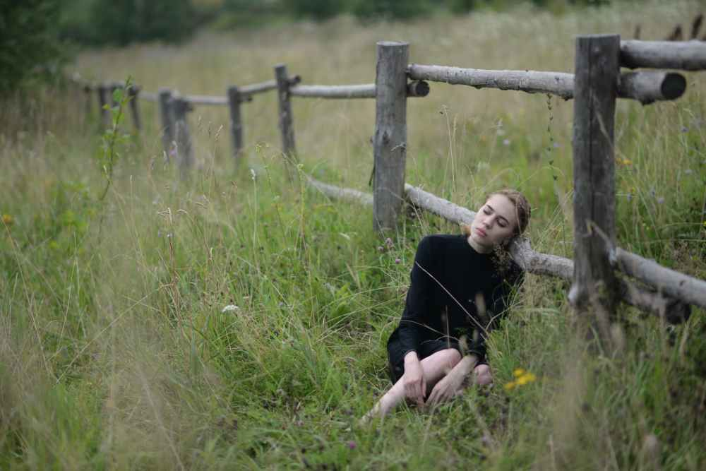woman laying on brown fence